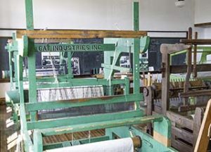 The second floor of the school contains a room full of looms, including this historic one from Gay Industries.